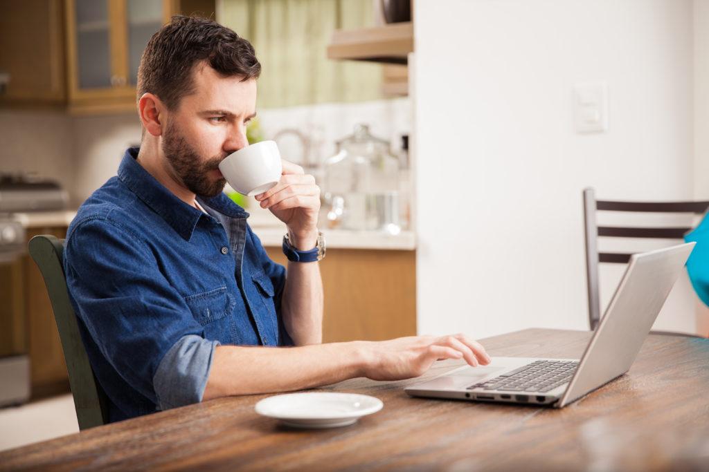 Mann mit Kaffee arbeitet zuhause am Laptop