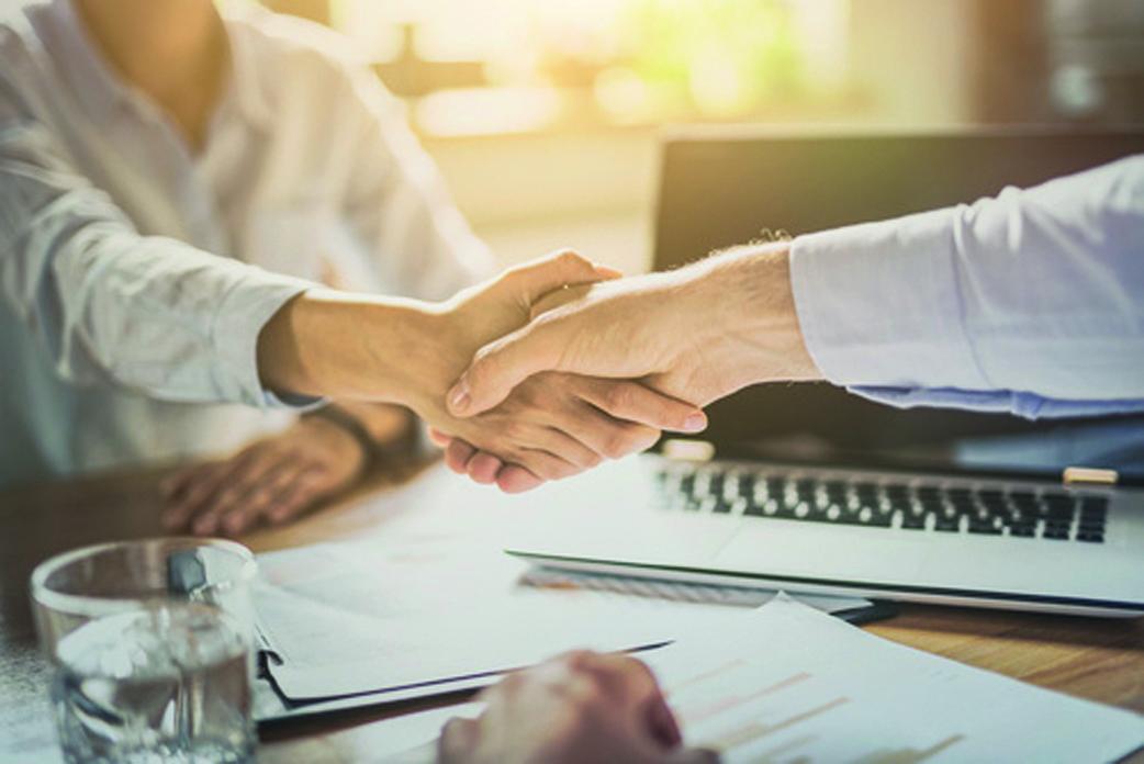 Zwei Geschäftsleute schütteln Hände, beenden ein Meeting.
